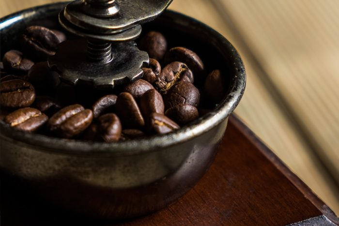Coffee beans in a hand grinder
